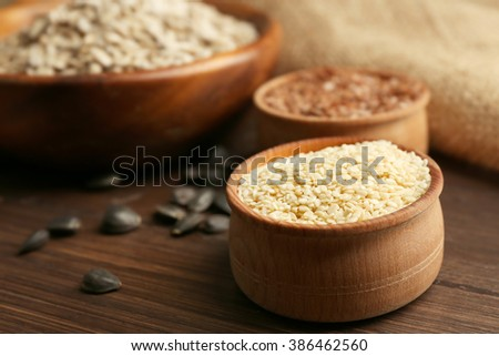 Sesame, flax and sunflower  seeds on wooden table background, closeup - stock photo