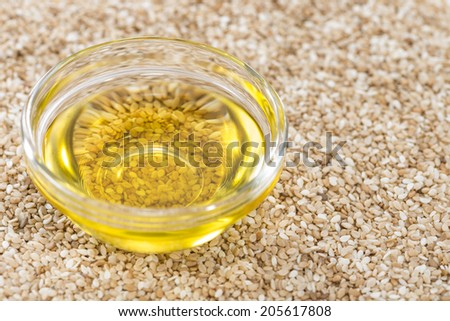 Sesame Oil in a small bowl on vintage wooden background (close-up shot) - stock photo