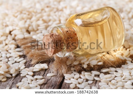 sesame seed oil in glass bottle on the table closeup horizontal  - stock photo