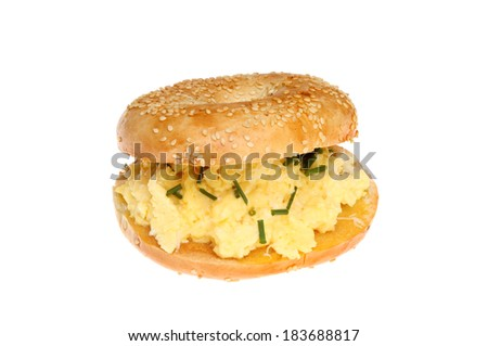 Sesame seeded bagel filled with scrambled egg topped with cheese and chives isolated against white