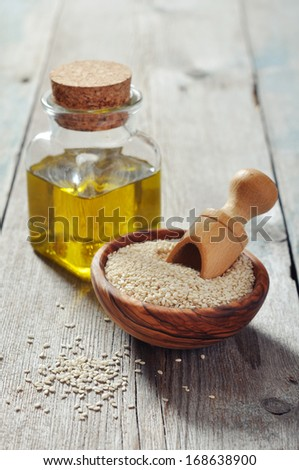 Sesame seeds and oil in bottle on wooden background - stock photo