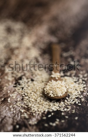 Sesame seeds close up into wood spoon