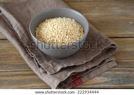 Sesame seeds in a bowl on wooden boards, closeup - stock photo