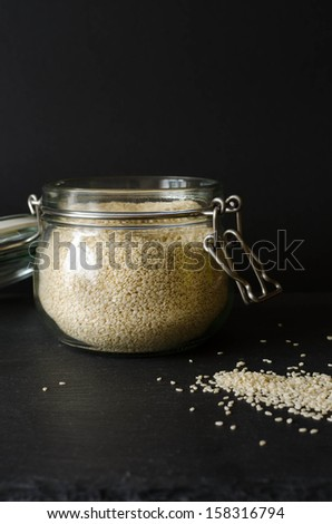 Sesame seeds in a jar, on a black background