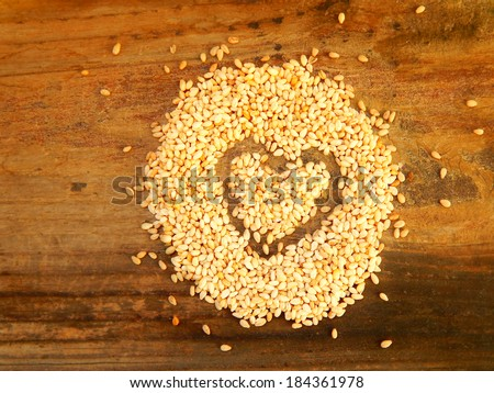 Sesame seeds in a shape of heart isolated on wooden background - stock photo