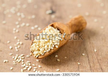 sesame seeds in a wooden scoop - stock photo