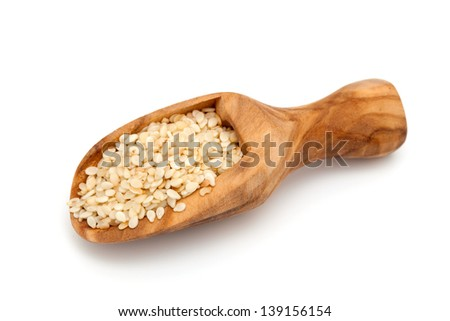 sesame seeds in a wooden scoop isolated on white background - stock photo