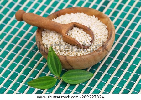 Sesame seeds in bamboo bowl, close up  - stock photo