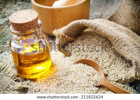 sesame seeds in sack and bottle of oil on wooden rustic table - stock photo