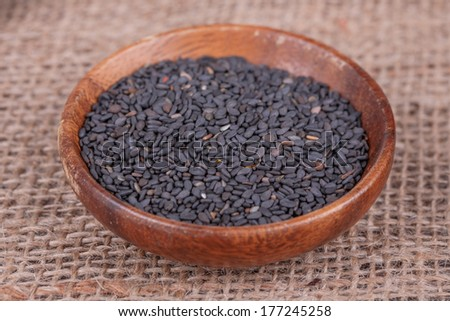 sesame seeds in wooden cup on  sack cloth - stock photo
