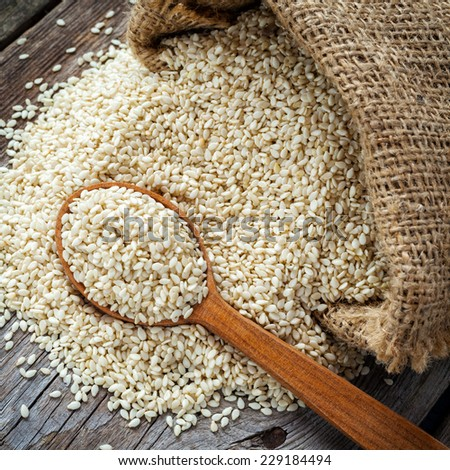 sesame seeds in wooden spoon and in sack on wooden rustic table, top view - stock photo