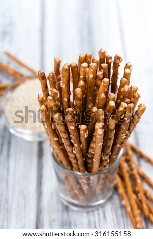 Sesame Sticks (close-up shot) on wooden background - stock photo