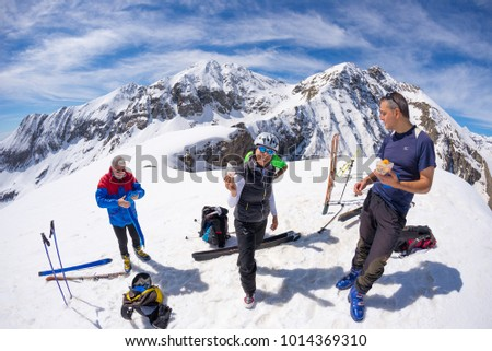 Sestriere, Italy - April 14, 2016: Group of alpinists selfie on mountain top. Scenic high altitude background on snow capped Alps, sunny day.