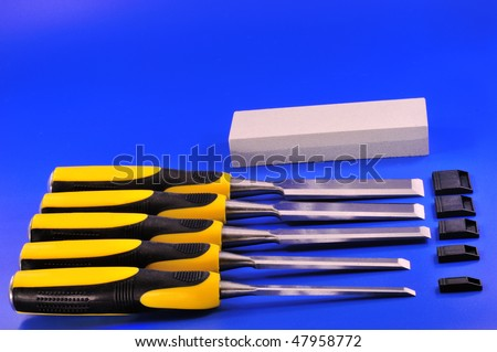 Set carpentry chisels with the black and yellow handles, and a stone for sharpening tools - stock photo