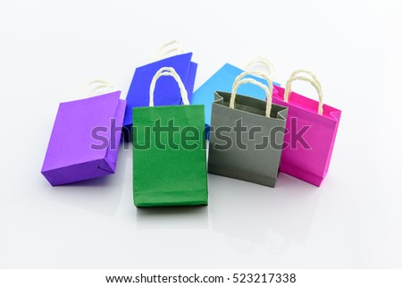 Set / collection of colorful paper shopping bags on a glossy white background. An idea for several things about shopping i.e. hypermarket special discount events, midnight sales, sales promotion, etc