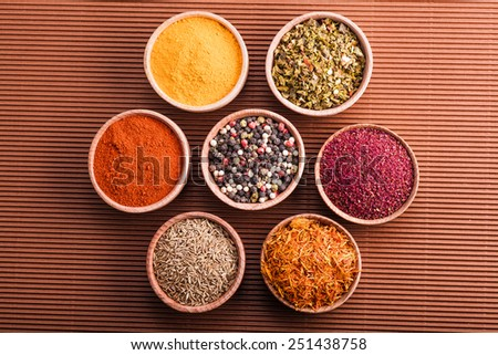 set dry spices in a wooden bowl on a brown background