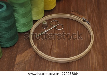 Set for embroidery of colorful threads, hoops, thimble and needle on background wooden table - stock photo