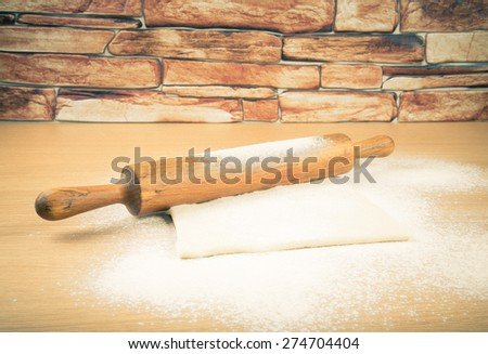 Set for home baking on a light wooden table with flour. Rolling pin and dough. Toned. - stock photo