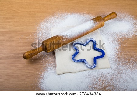 Set for home baking on a light wooden table with flour. Rolling pin, baking form, dough. - stock photo