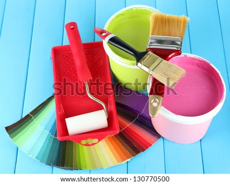 Set for painting: paint pots, brushes, paint-roller on blue wooden table - stock photo