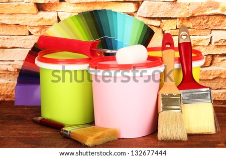 Set for painting: paint pots, brushes, paint-roller, palette of colors on stone wall background - stock photo