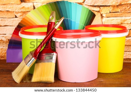 Set for painting: paint pots, brushes, palette of colors on stone wall background - stock photo