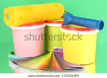 Set for painting: paint pots, paint-roller, palette of colors on green background - stock photo