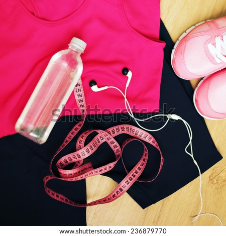 Set for sports activities. Running shoes and bottle of water, sport clothes and earphones isolated on wooden background. Photo toned style instagram filters.  - stock photo