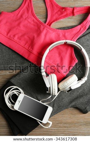 Set for sports and smart phone with headphones on wooden table background  - stock photo