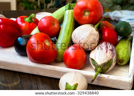 set fresh vegetables on a wooden tray for cooking. tomatoes, cucumber, blue and white eggplants, peppers, zucchini, - stock photo
