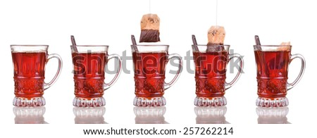 set, glass cup of black brown tea with spoon and tea bag isolated on white background - stock photo