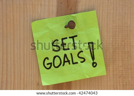 Set goals - motivational reminder on post note nailed to wooden plank or wall