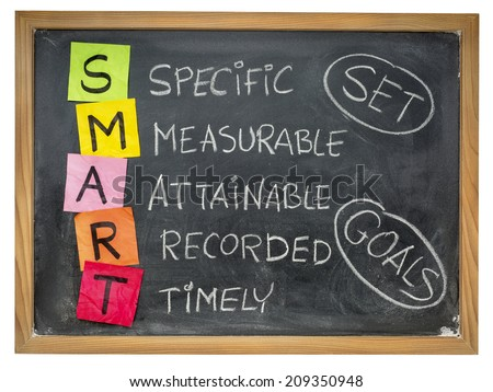 set goals SMART (specific, measurable, attainable, recorded, timely) colorful sticky notes and chalk handwriting on a blackboard - stock photo