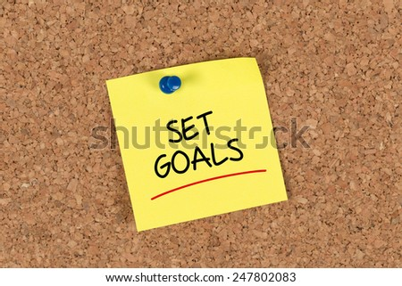 Set Goals written on a Yellow Sticky Note on a Cork Board