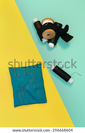 Set home seamstresses, thread and needles, blue and yellow background - stock photo