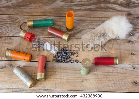 set hunting shotgun cartridges and a tail rabbit sober a wooden table  - stock photo