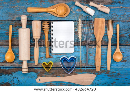 Set kitchen utensils and a notebook for recipes on a wooden background. - stock photo