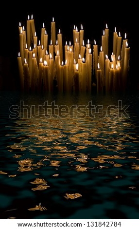 Set of a yellow votive candles burning in the dark. - stock photo