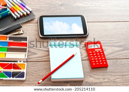 set of accessories for the modern pupil on a wooden table - stock photo