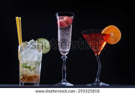 Set of alcoholic cocktails on black background.