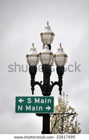 set of antique appearance street lights trimmed in gold and lampposts with directional sign of south and north main