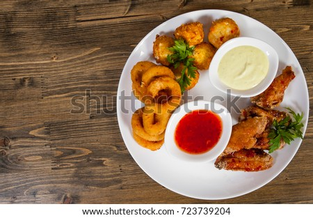 set of appetizers. salted balls, chicken wings, onion rings, sauce on a wooden background. with copy space. top view