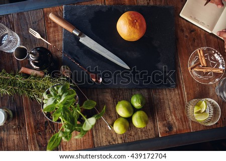 Set of bar accessories and ingredients for making a cocktail arranged on a wooden table - stock photo