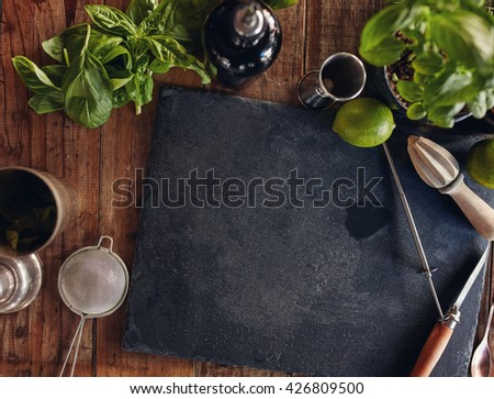 Set of bar accessories and ingredients for making a cocktail arranged on a wooden table with copy space on black board - stock photo