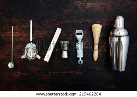 Set of bar or pub accessories with a martini cocktail shaker arranged in a neat line on a black background - stock photo