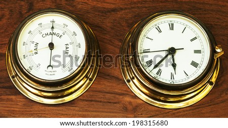 set of barometer and clock on wooden background - stock photo