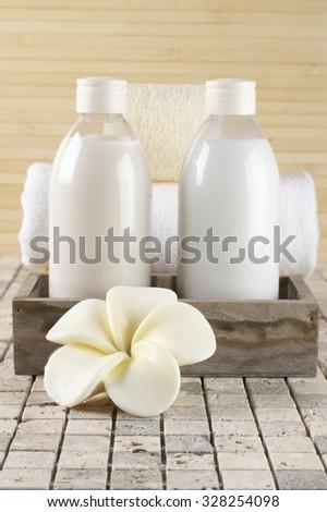 Set of bathroom accessory on stone tile: frangipani-shaped soap, shower gel, lotion, towel, loofah. Shallow DOF, focus on flower. - stock photo