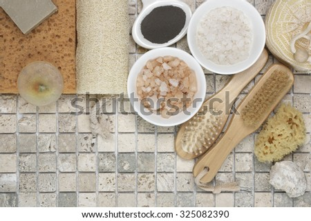 Set of bathroom accessory on stone tile: soaps, bath salt, clay, sponges, loofa. Top view point. - stock photo