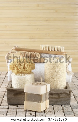 Set of bathroom accessory on stone tile: soaps stack, loofah, sponge, brushes, towel.