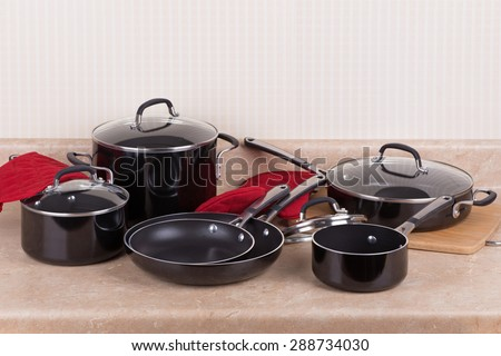 Set of black aluminum cookware on a kitchen counter - stock photo